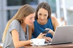 Dos amigos que comparten en la línea información en un teléfono foto de archivo libre de regalías