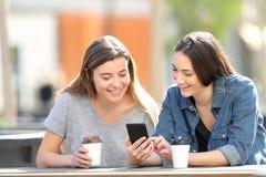 Dos amigos que comprueban el contenido en l?nea del tel?fono elegante en un parque fotos de archivo libres de regalías
