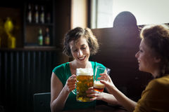 Dos amigos que consiguen la cerveza y el laughin de consumición del toghether, interiores Fotografía de archivo