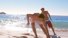 Dos amigos que corren en la playa metrajes