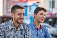 Dos amigos que cuelgan hacia fuera afuera en la ciudad en el fondo retro Foto de archivo