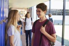 Dos amigos que hablan en pasillo de la escuela en el tiempo de la rotura fotografía de archivo libre de regalías