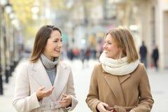 Dos amigos que hablan y que caminan en la calle Imagen de archivo