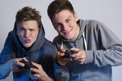 Dos amigos que hacen caras divertidas mientras que juega a los videojuegos Foto de archivo