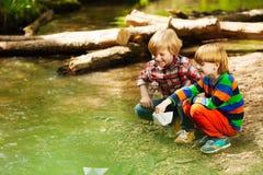 Dos amigos que juegan con los barcos de papel en la orilla del río imagenes de archivo