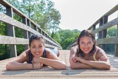 Dos amigos que mienten junto en el puente de madera Fotos de archivo