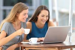 Dos amigos que miran el medios contenido en un ordenador portátil en una barra Fotografía de archivo