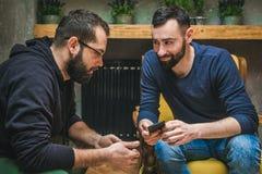 Dos amigos que miran el medios contenido en un teléfono elegante foto de archivo