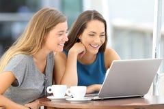 Dos amigos que miran fluyendo el contenido en línea Foto de archivo