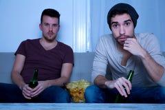 Dos amigos que miran la televisión en casa Imagen de archivo