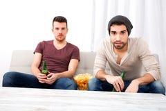 Dos amigos que miran la televisión en casa Fotos de archivo