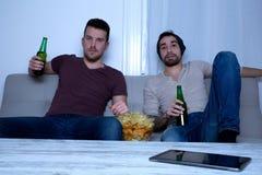 Dos amigos que miran la televisión en casa Imagenes de archivo