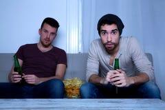 Dos amigos que miran la televisión en casa Foto de archivo