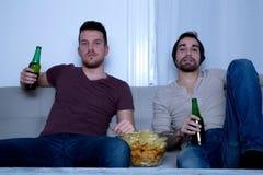 Dos amigos que miran la televisión en casa Foto de archivo libre de regalías