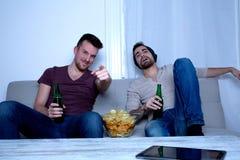 Dos amigos que miran la televisión en casa Imágenes de archivo libres de regalías