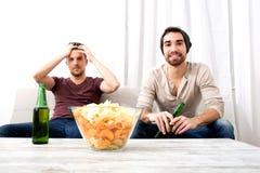 Dos amigos que miran la televisión en casa Fotos de archivo libres de regalías