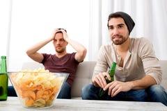 Dos amigos que miran la televisión en casa Imagen de archivo libre de regalías