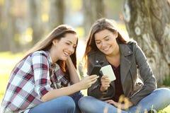Dos amigos que miran medios en sus teléfonos elegantes Imagen de archivo