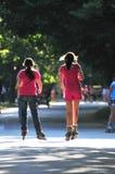 Dos amigos que montan patines en parque Fotos de archivo libres de regalías