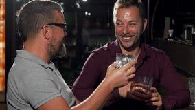 Dos amigos que ríen a la cámara mientras que teniendo bebidas junto metrajes