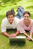 Dos amigos que ríen mientras que anticipa como utilizan una computadora portátil Imagen de archivo