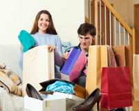 Dos amigos que sonríen con los bolsos después de hacer compras Foto de archivo libre de regalías