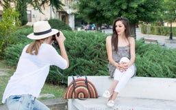 Dos amigos que toman imágenes en parque Foto de archivo