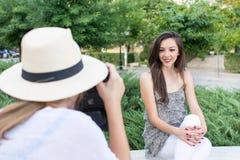 Dos amigos que toman imágenes en parque Imagen de archivo
