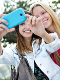 Dos amigos que toman las fotos con un smartphone Fotografía de archivo libre de regalías