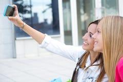 Dos amigos que toman las fotos con un smartphone Imágenes de archivo libres de regalías