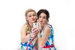 Dos amigos que toman un selfie con el teléfono elegante Fotos de archivo libres de regalías