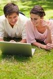 Dos amigos que usan una computadora portátil junto Imagen de archivo libre de regalías