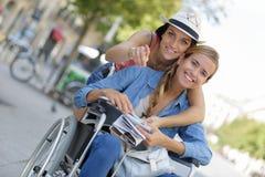 Dos amigos que visitan la ciudad extranjera una que se sienta en silla de ruedas Fotografía de archivo libre de regalías