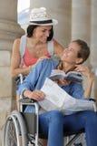 Dos amigos que visitan la ciudad extranjera una que se sienta en silla de ruedas Imagen de archivo