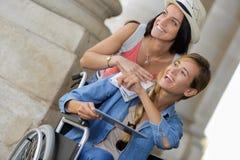 Dos amigos que visitan la ciudad extranjera una que se sienta en silla de ruedas Foto de archivo libre de regalías