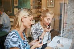 Dos amigos se sientan dentro del café resuelto para discutir el negocio, coffe de la bebida fotos de archivo libres de regalías