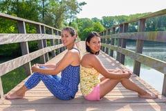 Dos amigos se sientan juntos en el puente de madera en naturaleza Fotografía de archivo