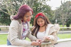 Dos amigos sonrientes de la mujer que comparten medios sociales en un teléfono elegante Imágenes de archivo libres de regalías