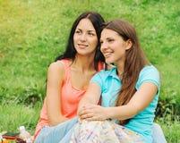 Dos amigos sonrientes felices de las mujeres en comida campestre en el parque Foto de archivo