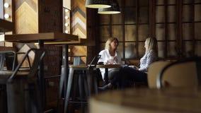 Dos amigos sonrientes que charlan en un café almacen de metraje de vídeo