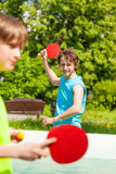 Dos amigos sonrientes que juegan junto al ping-pong Imágenes de archivo libres de regalías