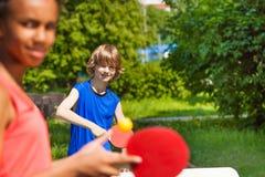 Dos amigos sonrientes que juegan juntos a tenis de mesa Imágenes de archivo libres de regalías