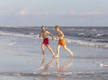 Dos amigos y hermanos adolescentes gozan el activar a lo largo de la playa Foto de archivo libre de regalías