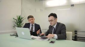 Dos analytics financieros masculinos discuten el informe anual en sitio de co-trabajo almacen de metraje de vídeo