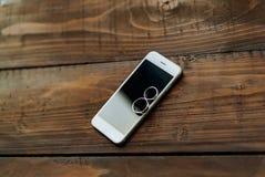 Dos anillo de bodas pone en un teléfono blanco en la tabla Los anillos de oro fueron comprados para la boda foto de archivo