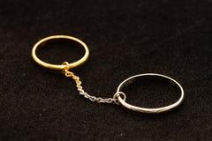 Dos anillos conectados por la cadena Foto de archivo libre de regalías