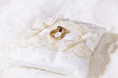 Dos anillos de bodas brillantes del oro junto en la almohada del cordón del satén Imagen de archivo libre de regalías