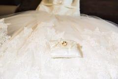 Dos anillos de bodas brillantes del oro junto en la almohada del cordón del satén Fotografía de archivo