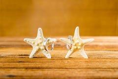 Dos anillos de bodas con dos estrellas de mar en la tabla de madera Imagenes de archivo
