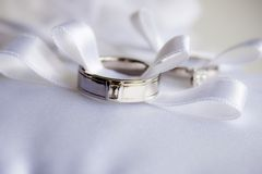 Dos anillos de bodas con el arqueamiento de la cinta imagen de archivo libre de regalías